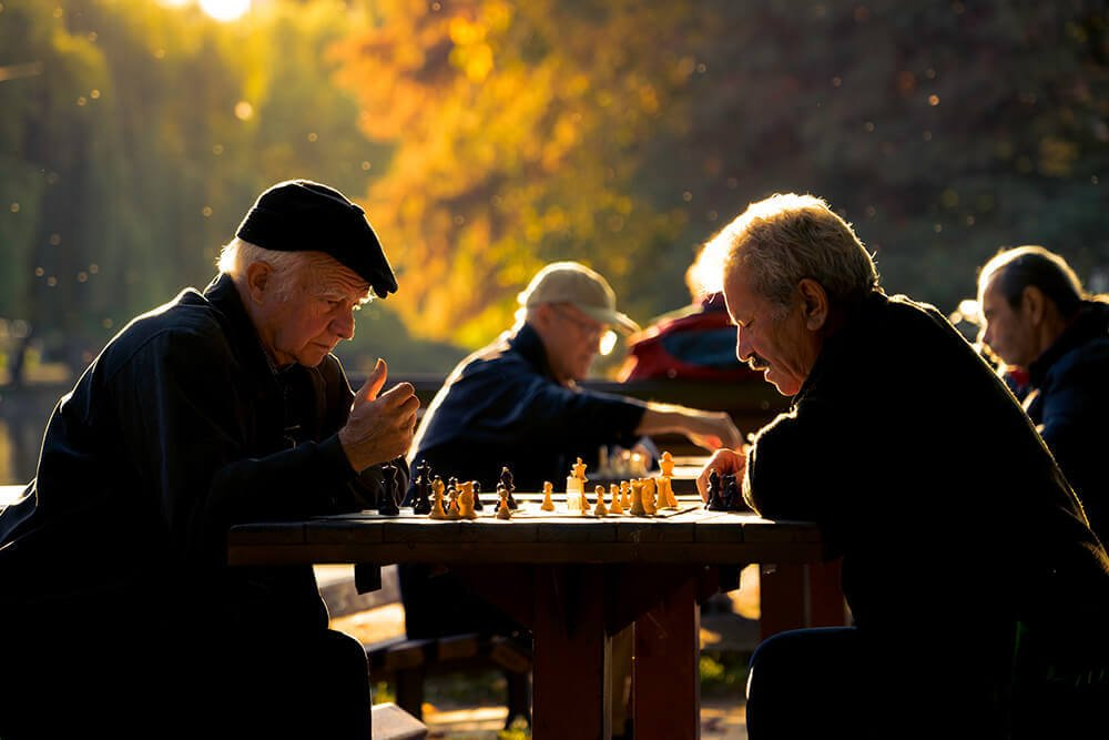 Two elderly men play chess in the park during the fall.