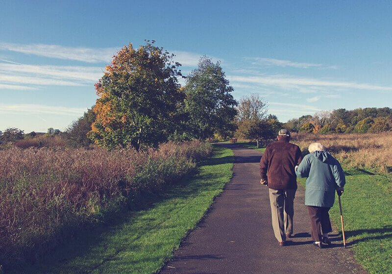 An elderly couple take a stroll down a walking path on a beautiful autumn day.