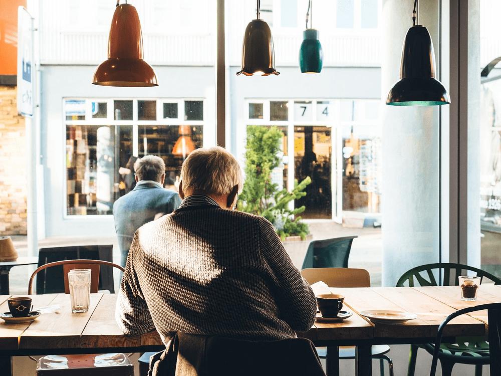 Senior man sits facing the window at a cafe