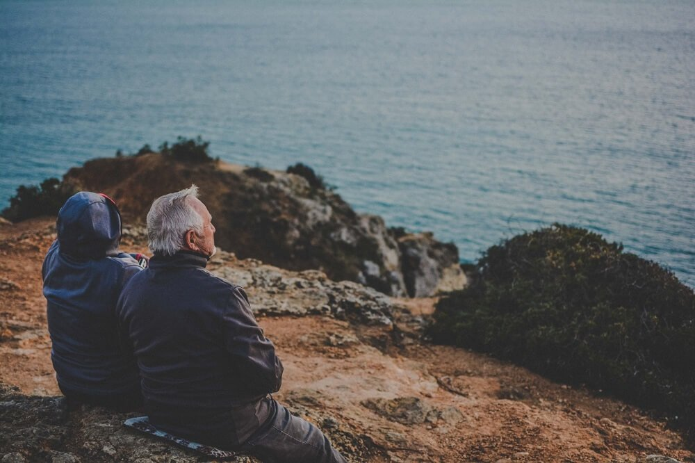 elderly couple sites on side of hill overlooking body of water