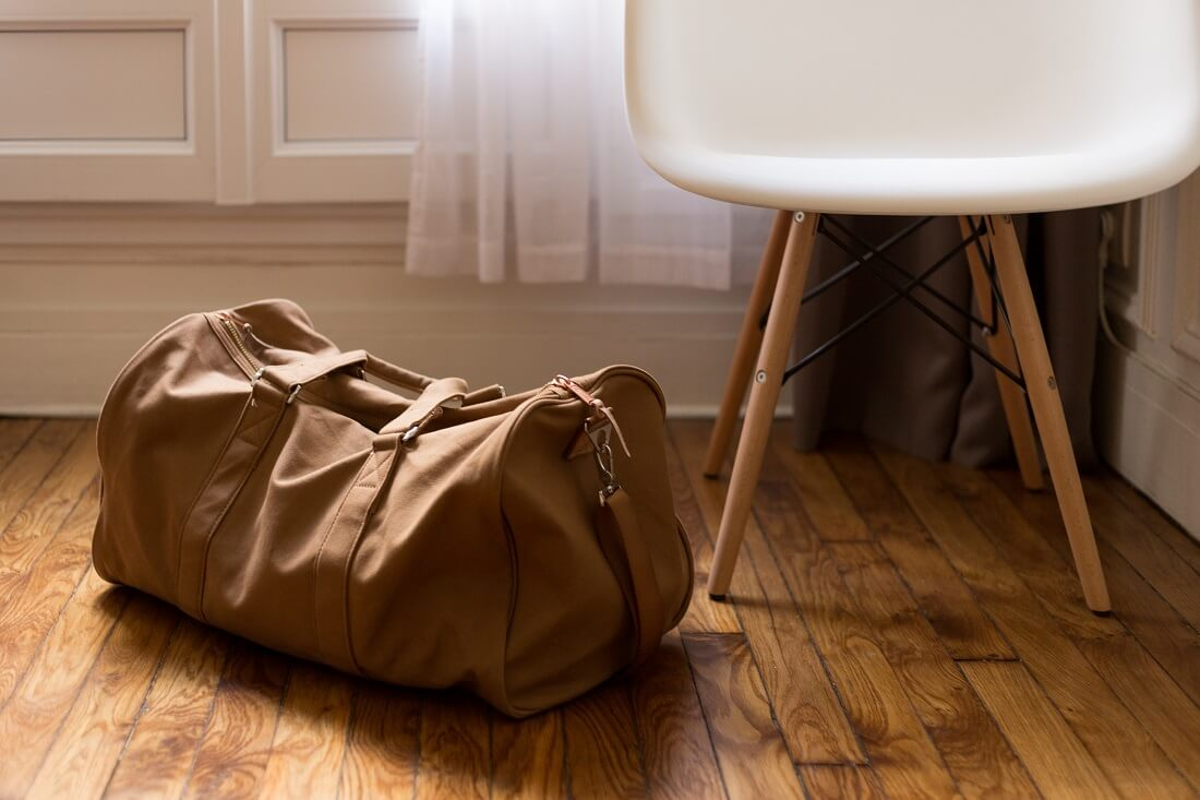 Brown duffel bag on a wooden floor next to a modern white chair