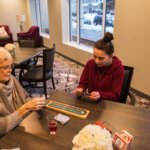 Elderly women playing cribbage with her daughter