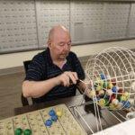 Elderly gentlemen rolling the bingo ball cage
